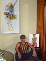 AponteSierra posing with two of his visual art pieces. over his right shoulder is a Paper Manipulated Fine Art piece. He is sitting next to a one Ink on Canvas